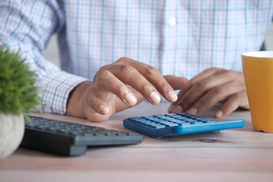man practising accounting with a calculator